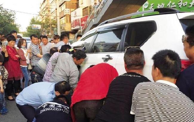 阜陽臨泉鬧市區 眾人抬車救人